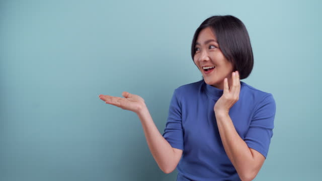 Happy asian woman present the copy space isolated on blue background. 4K video
