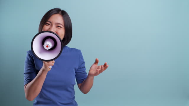 Happy asian woman used megaphone making shout gesture isolated on blue background. 4K video