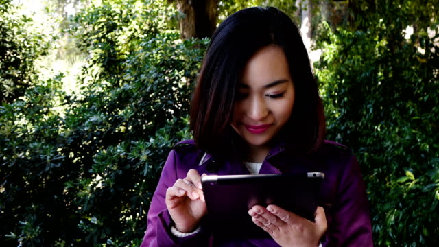 happy Asian woman using tablet pc computer in a park video