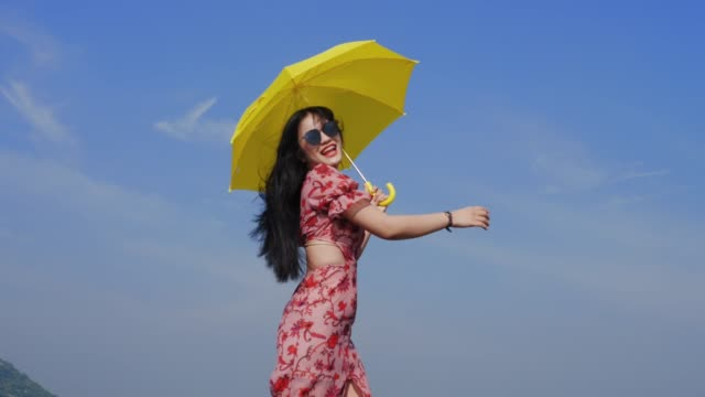 Happy Asian woman wearing sunglasses holding yellow umbrella against blue sky.