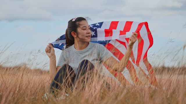 Happy asian woman with American flag USA celebrate 4th of July Happy asian woman with American flag USA celebrate 4th of July circa 4th century stock videos & royalty-free footage
