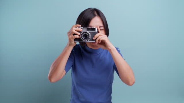 Happy asian woman with photo camera take a photo and looking at camera isolated over blue background 4K video video