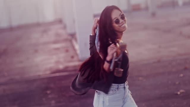 stockvideo's en b-roll-footage met gelukkig aziatische vrouw met skateboard ronddraaien in de stad - tienermeisjes