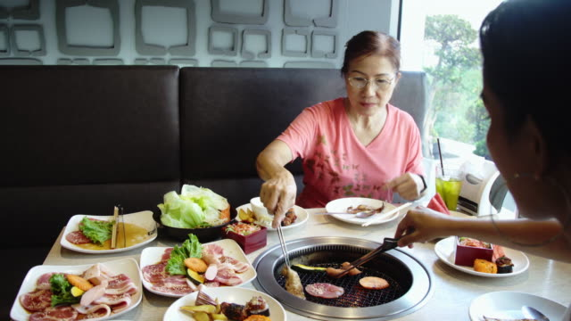 Happy Asian Women Grilling Barbecue Pork on Hot Coal Stove. Korean or Japanese BBQ Style.