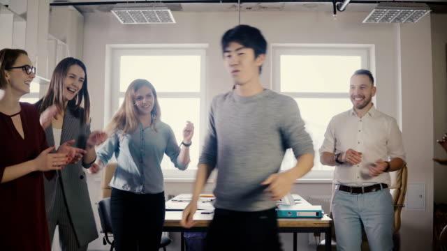 カジュアルなオフィス パーティーで踊る幸せなアジア青年実業家。日本人従業員は、同僚 4 k と勝利を祝う - 若者文化点の映像素材/bロール