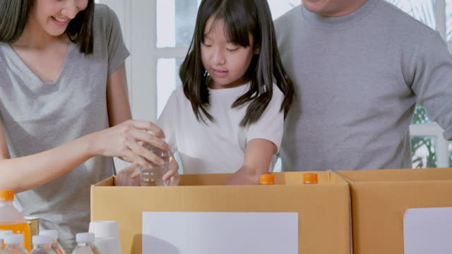 Happy asian young family of teaching little girl daughter about sustainability how packing to free food and drink for delivery into donate box at home.Teaching/learning about Donation Concept. - vídeo