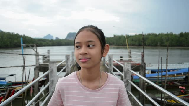 Happy asian young girl is walking leisurely and watching beautiful scenery at the pier in Phang Nga Bay.