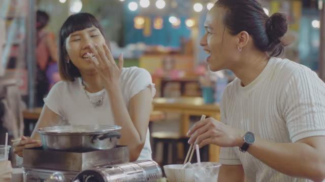 happy asian young group eating shabu shabu in the restaurant at night market. - cultura coreana video stock e b–roll