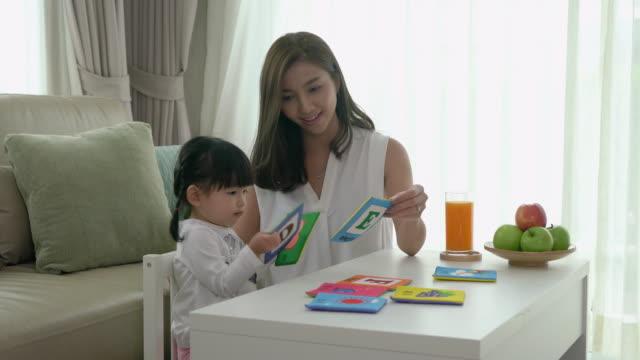 stockvideo's en b-roll-footage met gelukkig aziatische jonge moeder en dochter spelen met alfabet card, vroege onderwijs thuis. - baby toy