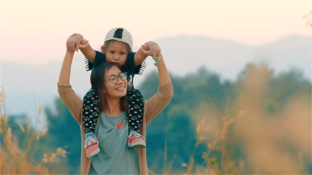 Happy Asian young mother carrying her daughter on her shoulder in the blurred field together video