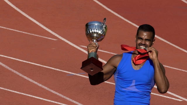 それを示す彼のメダルを噛んで幸せの選手が金、勝者の勝利を祝う - メダル点の映像素材/bロール