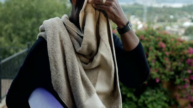 glad atletisk afroamerikansk kvinna torka svett av hennes ansikte efter träning - black woman towel workout bildbanksvideor och videomaterial från bakom kulisserna