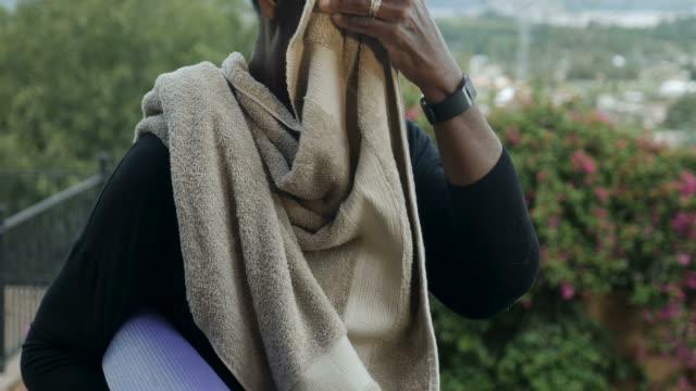 lycklig atletisk afroamerikanska kvinna torka svett av hennes ansikte efter träningen - black woman towel workout bildbanksvideor och videomaterial från bakom kulisserna
