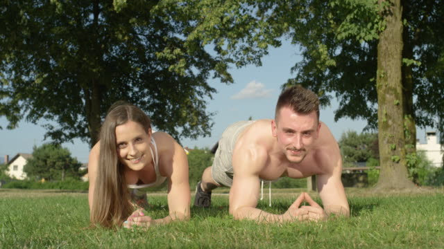 PORTRAIT: Happy athletic couple smiles while holding a plank in the green park.