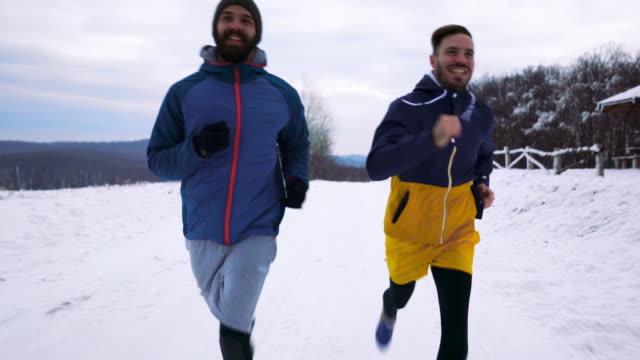 公園で雪の上を実行して幸せなスポーツマン。 - 体への関心点の映像素材/bロール
