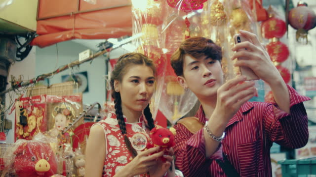 Happy attractive loving couple enjoy shopping together Asian travelers taking selfie with smartphone in Chinese New Year Festival at Yaowarat Road. Bangkok, Thailand. souvenir stock videos & royalty-free footage