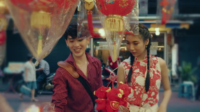 Happy attractive loving couple enjoy shopping together Asian travelers buying in gift in Chinese New Year Festival at Yaowarat Road. Bangkok, Thailand. souvenir stock videos & royalty-free footage
