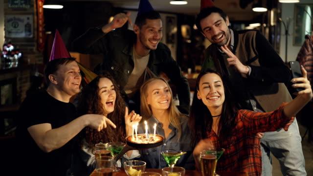 Felices alumnos atractivos en sombreros de fiesta de cumpleaños grabe video con smartphone sentado en la mesa en la barra. Posando con la torta, hablando y riendo. - vídeo