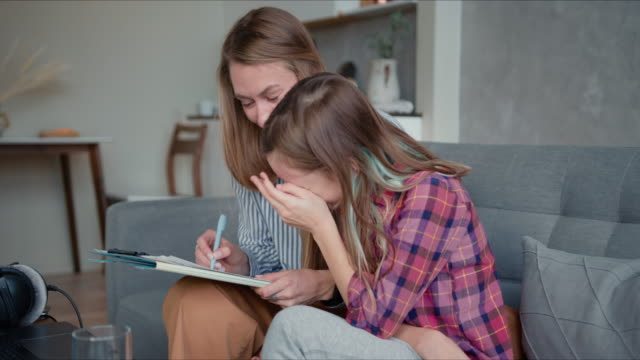 Happy attractive young Caucasian mother helping cute cheerful teenage daughter study and learn on quarantine at home. video