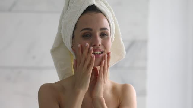 stockvideo's en b-roll-footage met gelukkige aantrekkelijke jonge vrouw met handdoek op hoofd aanraken gezicht - vrouw schoonmaken