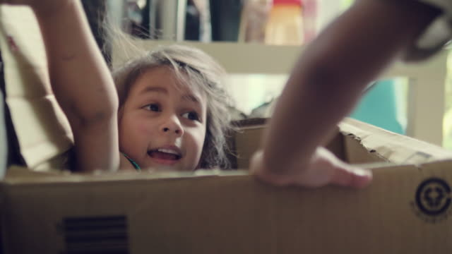 vídeos de stock e filmes b-roll de happy baby and her sister playing in cardboard box. - cardboard box