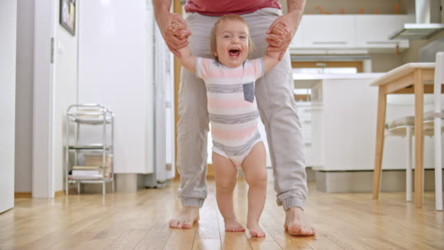 SLO MO Happy baby boy learning to walk with his father video