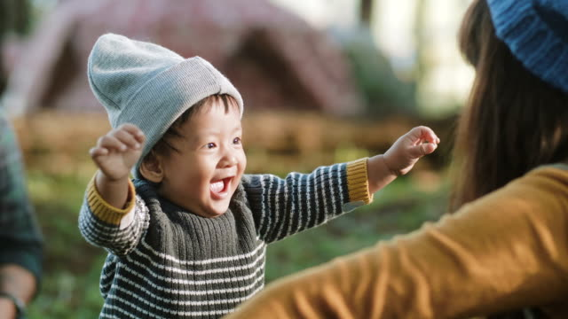 Happy baby boy making his first steps on grass in forest.