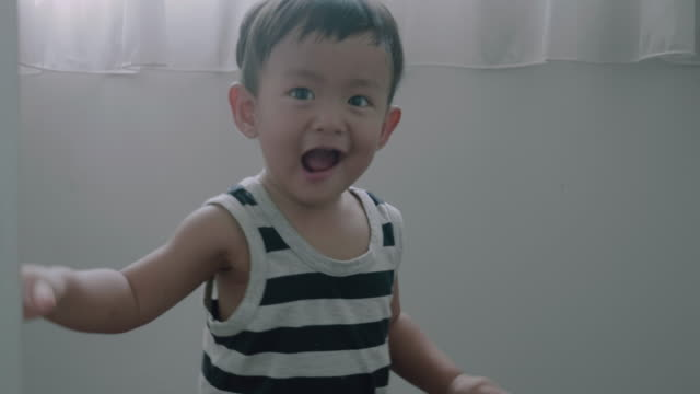 Happy baby boy playing hide and seek at home video