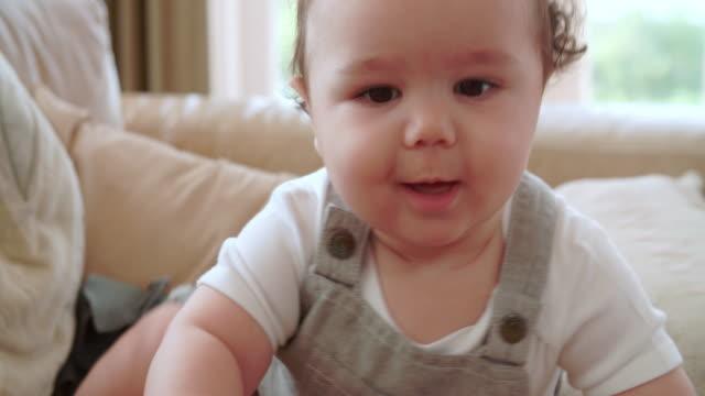 bambino felice ragazzo giocando sul divano di casa - solo neonati maschi video stock e b–roll