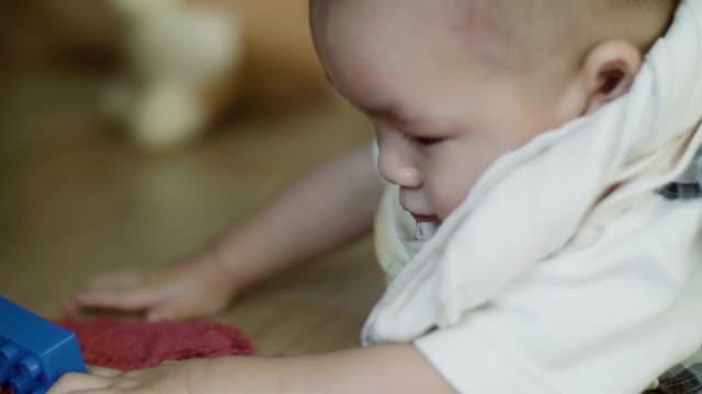 happy baby boy playing on the floor - solo neonati maschi video stock e b–roll