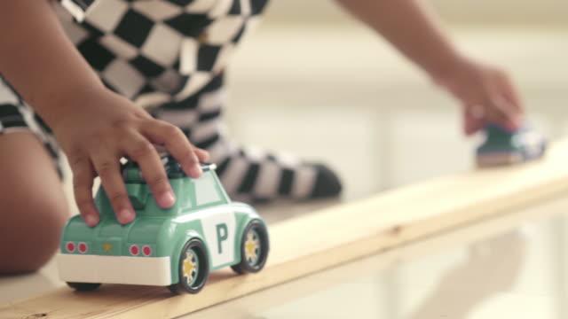 Happy baby boy playing toy car
