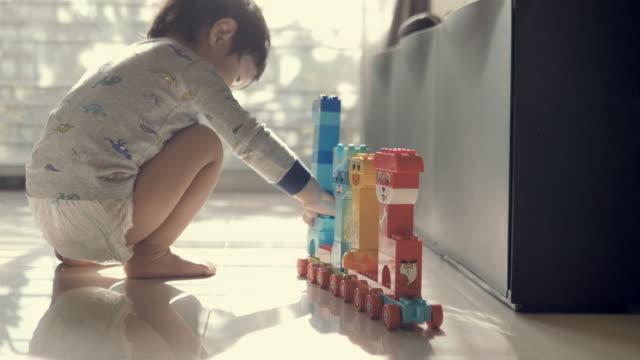 happy baby boy playing with blocks - klocek filmów i materiałów b-roll