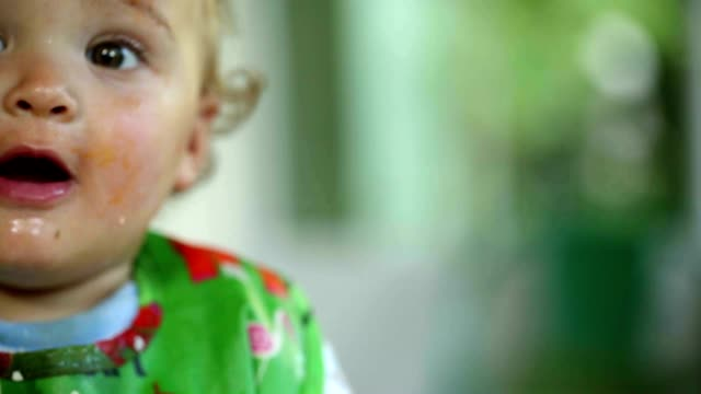 vídeos de stock e filmes b-roll de happy baby dirty from eating supper / lunch. messy toddler baby during lunch - boca suja