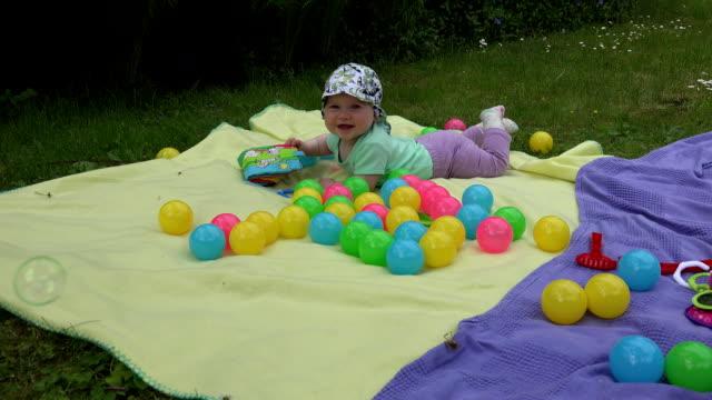 happy baby enjoy flying soap bubbles on meadow. FullHD video