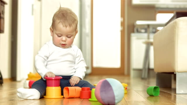 stockvideo's en b-roll-footage met happy baby girl playing with blocks - baby toy