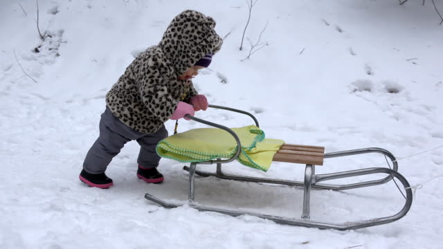 Happy baby girl push sledge on snow in winter park. Handheld. video