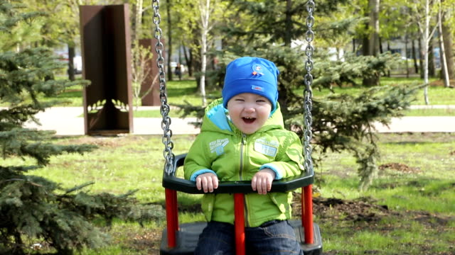Happy baby laughing on a swing video