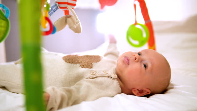 Happy baby playing in baby gym toy