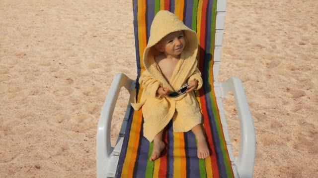 vídeos de stock e filmes b-roll de happy baby with bathrobe and sunglasses smiling, laughing at seaside - bebé praia