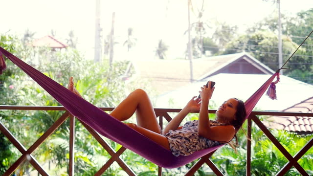 happy beach woman reading sms texting on smartphone lying on hammock relaxing on tropical vacation. slow motion. 1920x1080 - amaca video stock e b–roll
