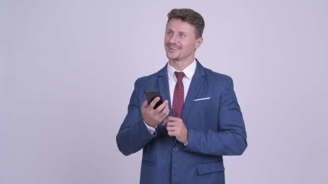 Feliz empresário barbudo de terno pensando enquanto usa telefone - vídeo