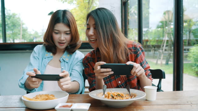 Happy beautiful Asian friends women blogger using smartphone photo and making food vlog video for her subscribers and her channel at cafe.