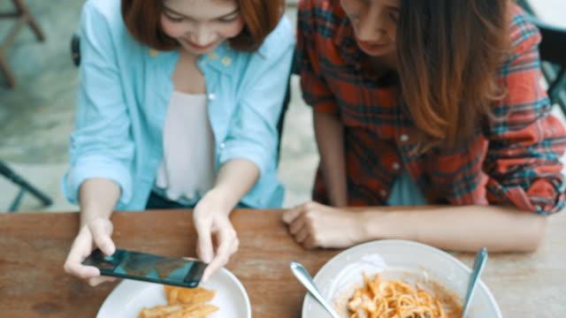 vídeos de stock, filmes e b-roll de feliz amigos asiáticos belas mulheres blogger usando smartphone foto e fazendo comida vlog vídeo para seus assinantes e seu canal no café. - blogar