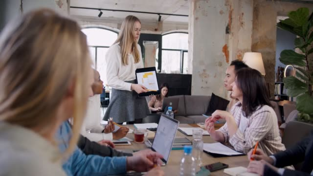 Happy beautiful blonde 20s female IT coach using tablet to pitch ideas at modern light multiethnic loft office meeting. video