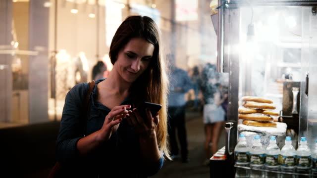 vídeos de stock, filmes e b-roll de feliz bonito caucasiano feminino blogger usando smartphone compras app perto de caminhão de comida de rua com pretzels em nova york - blogar