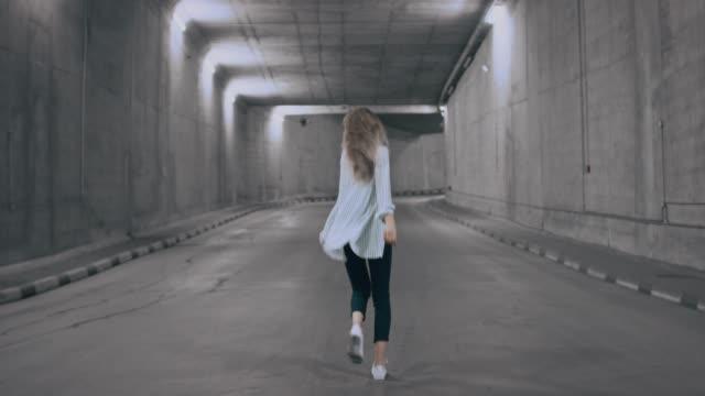 happy beautiful cool ung blond kvinna är promenader och dans i en upplyst betong tunnel. hon är klädd i en randig vit skjorta och dark jeans. - street dance bildbanksvideor och videomaterial från bakom kulisserna