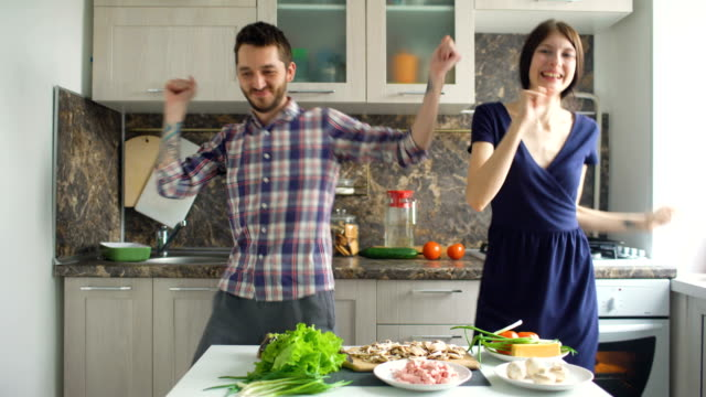 Happy beautiful couple dancing rocknroll while cook on the kitchen at home - Vidéo