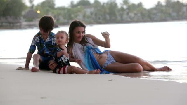 lycklig vacker mode familj, barn, klädd i hawaiiskjortor, leker tillsammans på stranden på solnedgången, familje förmåner glad semester - förskoleelev bildbanksvideor och videomaterial från bakom kulisserna