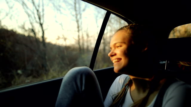 Happy, beautiful girl is looking outside a moving car