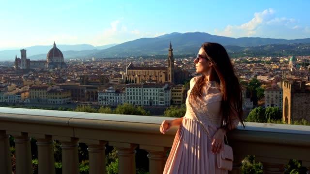 Happy beautiful girl taking photos at amazing Florence panorama, Italy.